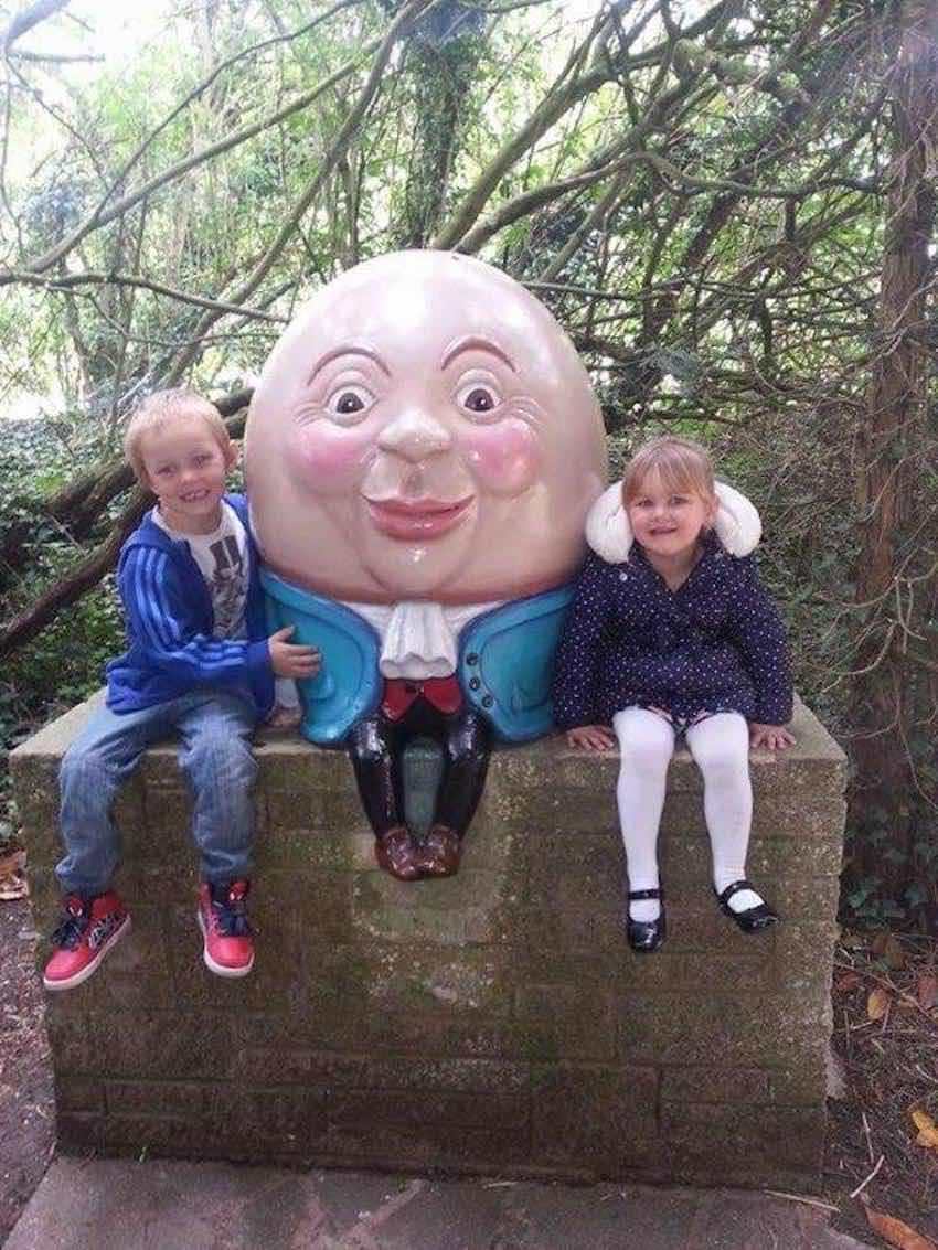 Humpty Dumpty sitting on a wall with two happy visitors at Sundown Adventureland